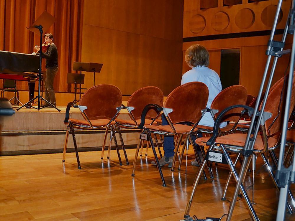 Bild einer leeren Bühne mit wenigen Pulten und Stühlen